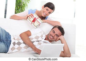 Woman handing gift to man on sofa