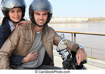 Young couple on a moped by a river