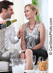 Two smartly dressed people about to drink champagne