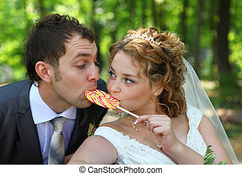 Groom and bride eating candy together in summer forest