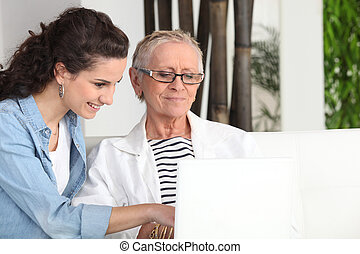 Younger and older woman sitting at a laptop