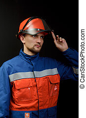 The worker in overalls and a helmet