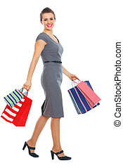 Full length portrait of happy woman with shopping bags