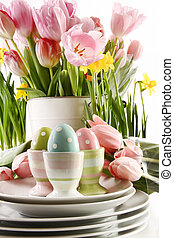 Easter eggs in cups with spring flowers on white background