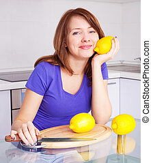 woman with lemons - pretty young woman with lemons in the...