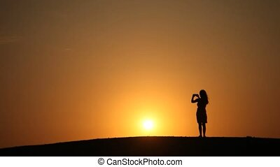 Woman takes picture of Sunset