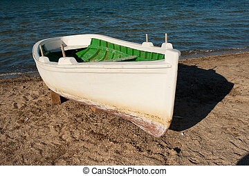 Fishing boat - Small white fishing boat on a beach