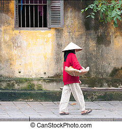 Hoi An street seller - Vietnamese seller walking on the...