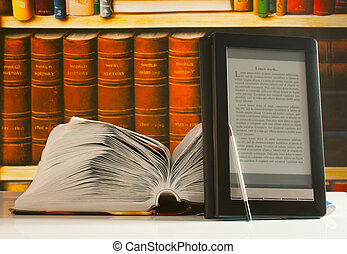 Open book and electronic book reader laying on the table
