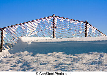 Fence covered with hoar frost against a blue sky