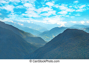 Green mountains with forest and blue cloudy sky
