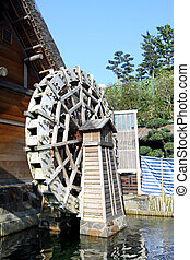 Water wheel next to a house