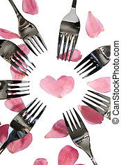 silver forks surrounding heart shape and rose petals