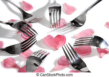 stylish forks surrounding heart shape and rose petals -...