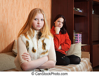 girls having quarrel at home - Two sad girls having quarrel...