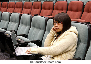 Asian student studying in lecture hall with laptop