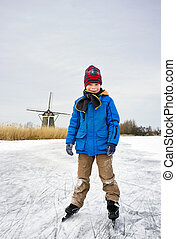 Ice Skating boy - Young child, skating and smiling into the...