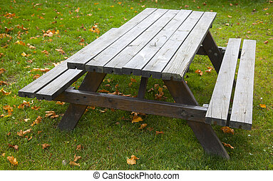 Wood table with benches on grass - An empty wood table with...
