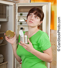 woman putting with metal can near fridge - Young woman...