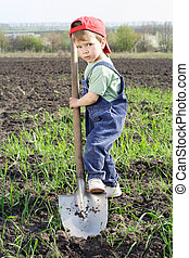 Little boy to dig on field with big shovel, looking to...