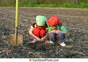 Little children with shovel on field looking to ground