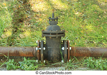 old rusty pipe with shut-off valve over green grass