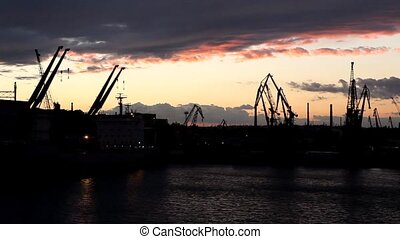 shot during sunset - Silhouette of several cranes in a...