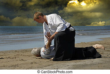 Aikido - Two adults are training in Aikido on the beach