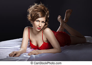 Sexy woman in red posing on white silk bed