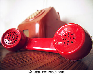 Old red telephone on wood table and white wall
