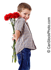 Smiling boy hiding a bouquet of red carnations behind...