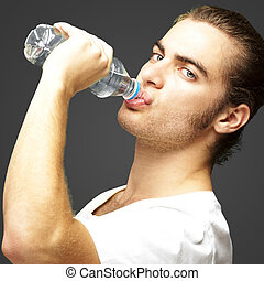 man drinking water - portrait of young man drinking water...