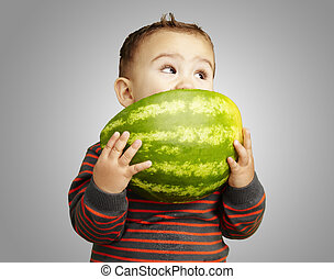 portrait of a handsome kid holding watermelon and sucking...