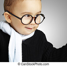 portrait of adorable kid gesturing doubt against a grey backgrou