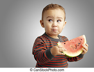 portrait of a handsome kid holding a watermelon and tasting...