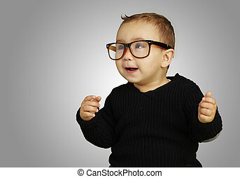 portrait of adorable kid wearing glasses and gesturing over grey