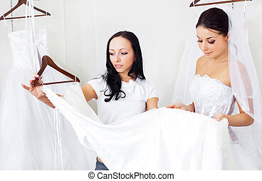 girl choosing a wedding dress - pretty young women choosing...