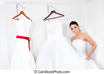 girl choosing a wedding dress - pretty young woman is...