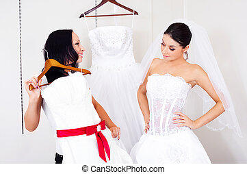 girl choosing a wedding dress - pretty young women choosing...