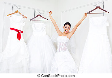 girl choosing a wedding dress - pretty young excited woman...