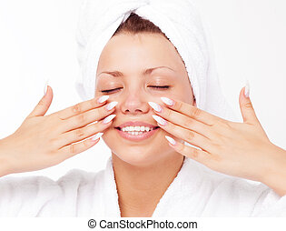 face massage - beautiful young woman wearing a towel and a...
