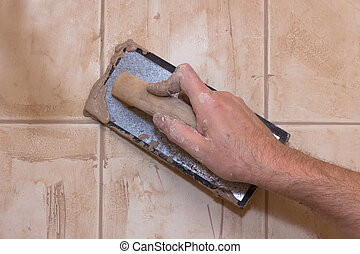 Tile and Grout - Hand holding a tile grout tool