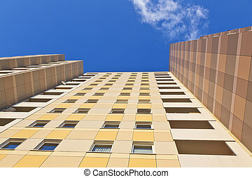 facade of skyscraper with apartments with blue sky