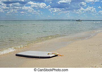 Boogie board on beach - Boogie board on sandy beach in calm...