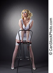 Sensuality gold blond woman stand with bar chair