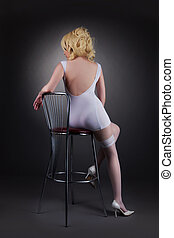 Sexy gold blond woman sit on chair