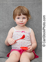 Portrait of small girl playing on couch with spoon and plate toys