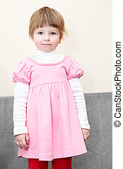 Portrait of small girl in pink dress standing on couch and looking