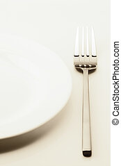 Set of tableware - Empty white plate and fork on light...