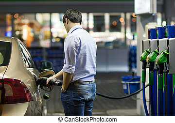 Young man fueling his car at the gas station